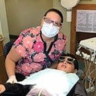 Dental assistant with child in dental exam room