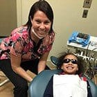 Assistant and smiling little girl in dental exam room