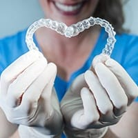 dental team member holding two Invisalign trays in the shape of a heart