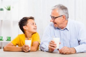 child and grandfather drinking milk