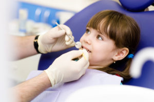 Young girl receiving fluoride treatment