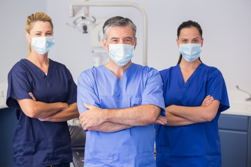 Dental team wearing scrubs and face masks